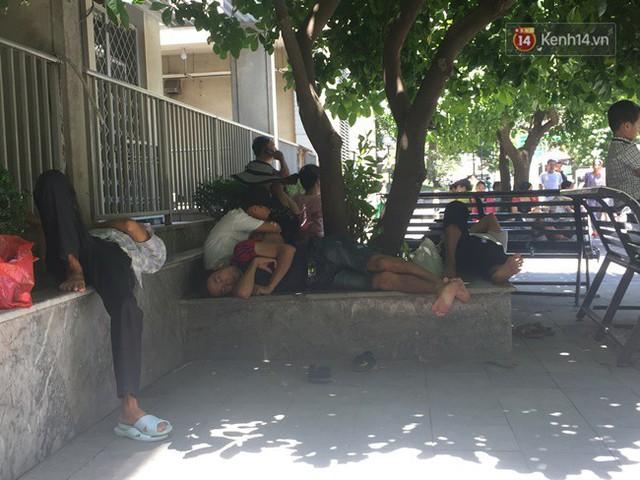 Ảnh: Người nhà bệnh nhân vạ vật gần hành lang, dưới bóng cây trong bệnh viện để tránh nắng nóng đỉnh điểm trên 40 độ ở Hà Nội - Ảnh 5.