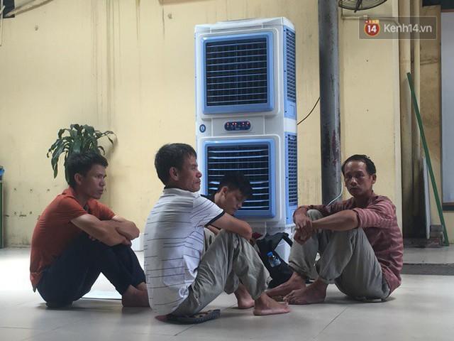Ảnh: Người nhà bệnh nhân vạ vật gần hành lang, dưới bóng cây trong bệnh viện để tránh nắng nóng đỉnh điểm trên 40 độ ở Hà Nội - Ảnh 7.