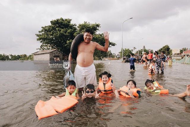 Nước vừa rút lại lên, người già trẻ nhỏ tiếp tục ùa ra đường tỉnh lộ vô tư bơi lội khi phương tiện bị cấm lưu thông - Ảnh 13.