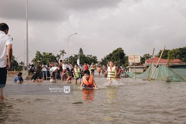 Nước vừa rút lại lên, người già trẻ nhỏ tiếp tục ùa ra đường tỉnh lộ vô tư bơi lội khi phương tiện bị cấm lưu thông - Ảnh 14.