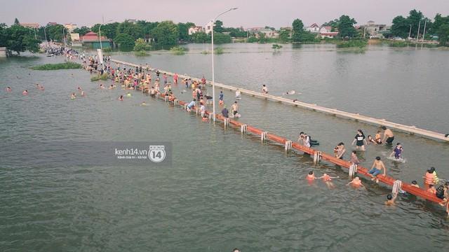 Nước vừa rút lại lên, người già trẻ nhỏ tiếp tục ùa ra đường tỉnh lộ vô tư bơi lội khi phương tiện bị cấm lưu thông - Ảnh 17.