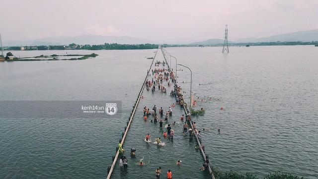 Nước vừa rút lại lên, người già trẻ nhỏ tiếp tục ùa ra đường tỉnh lộ vô tư bơi lội khi phương tiện bị cấm lưu thông - Ảnh 7.