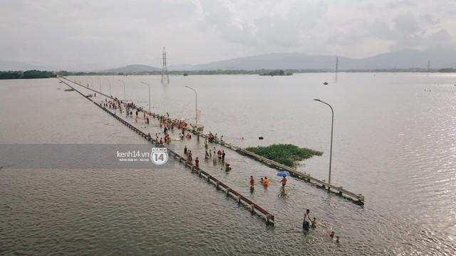 Nước vừa rút lại lên, người già trẻ nhỏ tiếp tục ùa ra đường tỉnh lộ vô tư bơi lội khi phương tiện bị cấm lưu thông - Ảnh 9.