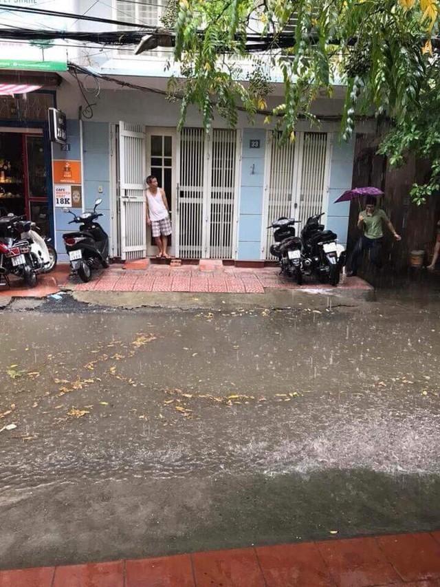 Người Hà Nội đứng giữa đường đón mưa vàng sau nhiều ngày nóng 40 độ C - Ảnh 1.