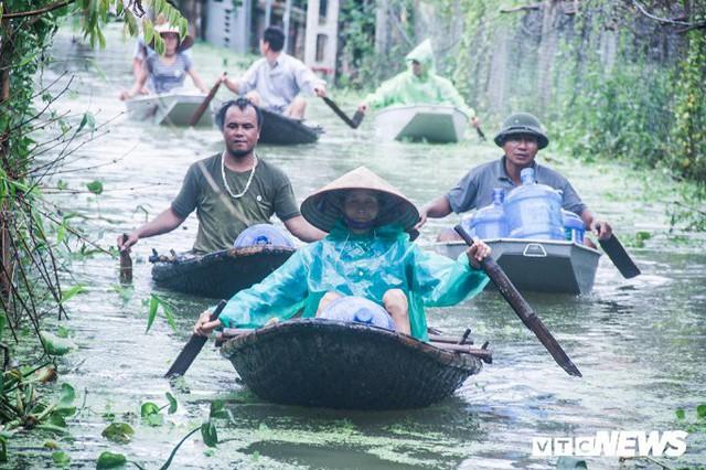 Dân vùng rốn lũ Hà Nội tấp nập chèo thuyền đi lấy nước miễn phí - Ảnh 1.