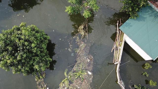 Rác thải cùng nước len lỏi vào nhà dân vùng rốn lũ Hà Nội  - Ảnh 1.