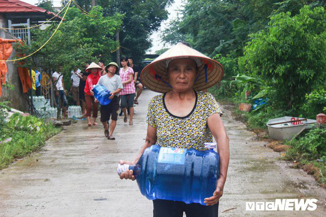 Dân vùng rốn lũ Hà Nội tấp nập chèo thuyền đi lấy nước miễn phí - Ảnh 5.