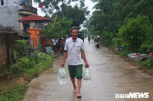 Dân vùng rốn lũ Hà Nội tấp nập chèo thuyền đi lấy nước miễn phí - Ảnh 6.