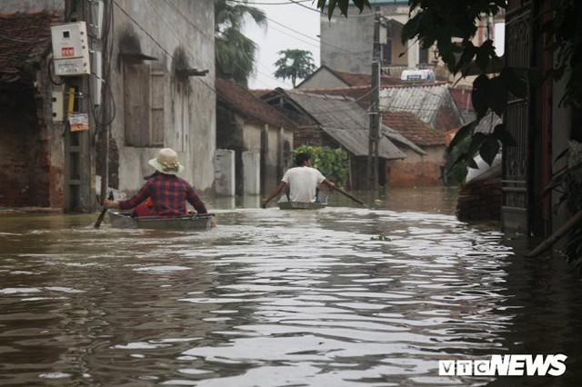 Dân vùng rốn lũ Hà Nội tấp nập chèo thuyền đi lấy nước miễn phí - Ảnh 10.