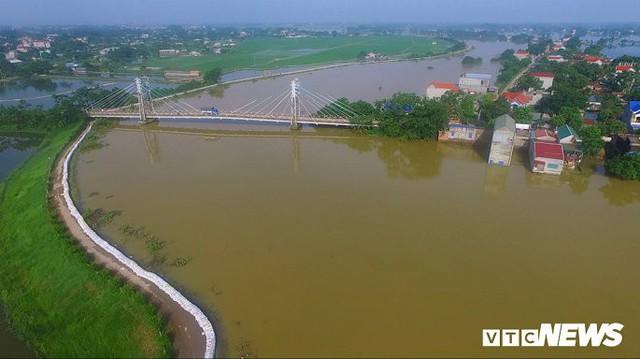 Video Flycam: Nước ngập đầu người, dân Thủ đô đi lại trên mái nhà lấy đồ cứu trợ - Ảnh 2.