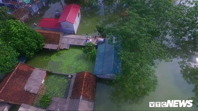Video Flycam: Nước ngập đầu người, dân Thủ đô đi lại trên mái nhà lấy đồ cứu trợ - Ảnh 6.