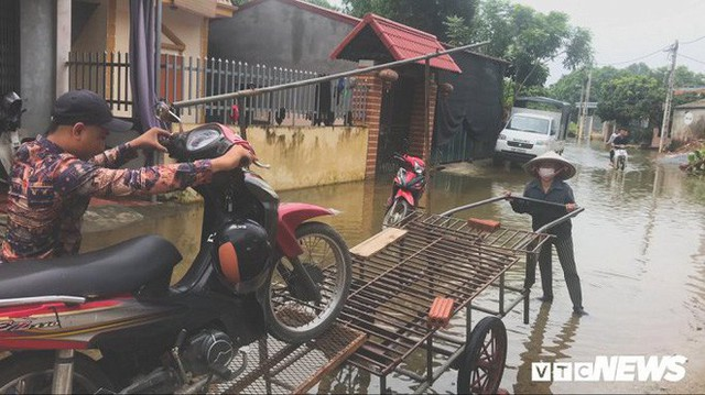 Video Flycam: Nước ngập đầu người, dân Thủ đô đi lại trên mái nhà lấy đồ cứu trợ - Ảnh 9.