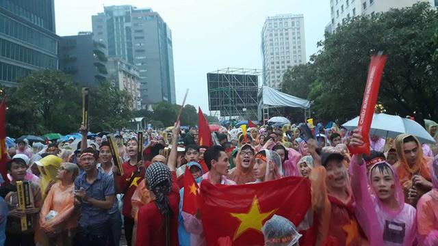 Người Sài Gòn nổi lửa giữa mưa ở phố đi bộ Nguyễn Huệ cổ vũ Olympic Việt Nam - Ảnh 1.