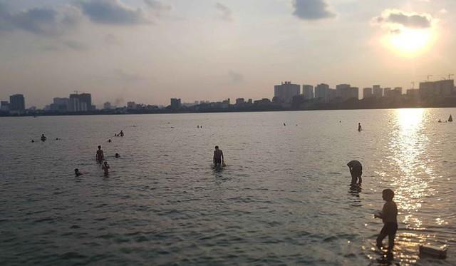 Người dân đổ ra Hồ Tây tắm, mặc cá chết bốc mùi tanh nồng  - Ảnh 1.