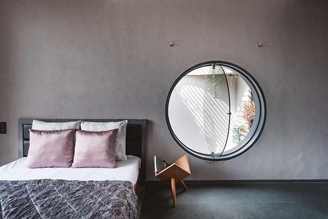 Phòng ngủ tuyệt đẹp với cửa sổ hình tròn mở ra khu vực giếng trời.