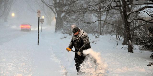 Người dân Canada dọn tuyết ra khỏi đường xe chạy để đảm bảo an toàn giao thông.