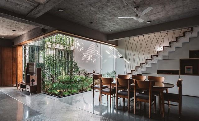 Tầng 1 được thiết kế đơn giản với các khu vực chức năng chung như bếp, khu vực ăn uống, phòng khách và một phòng ngủ. Một góc giữa nhà được dùng để làm giếng trời với khung kính bao quanh manh nắng gió cho khắp không gian.