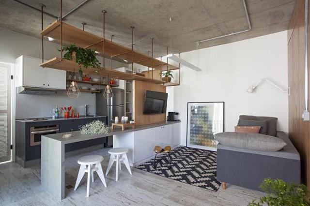 Bước chân vào căn hộ này, ấn tượng đầu tiên đó chính là giá treo bằng gỗ phân chia giữa không gian bếp và phòng khách.