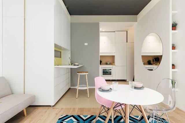 Bên hông chiếc tủ đặc biệt này còn đượ thiết kế những cánh tủ có thể dễ dàng lật ra để làm bàn để đồ, bàn ăn thuận tiện. Chiếc giương tròn vừa là điểm nhấn trang trí nhưng cũng góp phần nhân đôi diện tích góc nhỏ này.