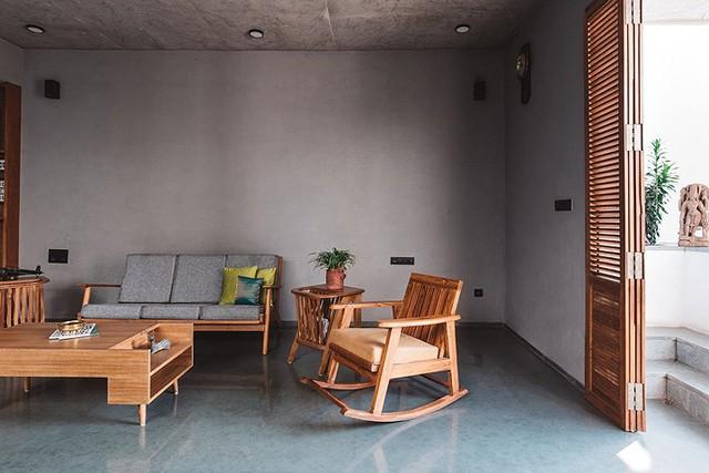 Phòng khách đơn giản với ghế băng dài, ghế bập bênh và một bàn trà gỗ đặt ngay cạnh lối vào nhà. Toàn bộ tường và trần nhà để thô kết hợp nội thất gỗ tạo nét không gian vừa xưa cũ vừa hiện đại độc đáo cho công trình.