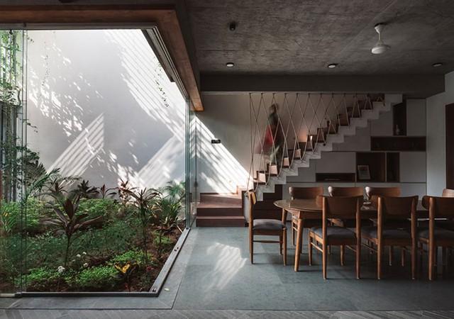 Khu vực giếng trời được bao bọc bằng ửa kính có thể dễ dàng đóng mở để mang nắng gió tràn ngập ngôi nhà. Cầu thang dẫn lên tầng 2 có lan can thiết kế bằng dây cáp thông thoáng.
