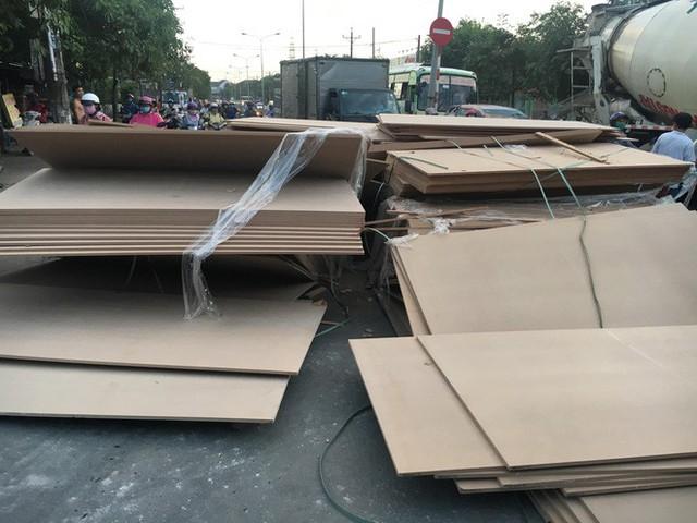 Hàng trăm tấm gỗ ép trên xe container lao xuống đường, nhiều người thoát chết - Ảnh 1.