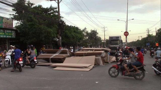 Hàng trăm tấm gỗ ép trên xe container lao xuống đường, nhiều người thoát chết - Ảnh 3.