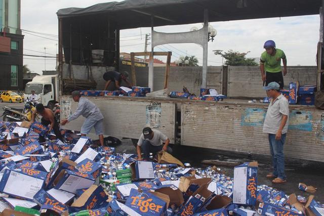 Hàng trăm thùng bia rơi xuống đường, người dân phụ tài xế thu gom - Ảnh 1.