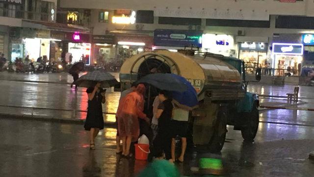 Cư dân Linh Đàm đội mưa nhọc nhằn hứng từng can nước  - Ảnh 1.