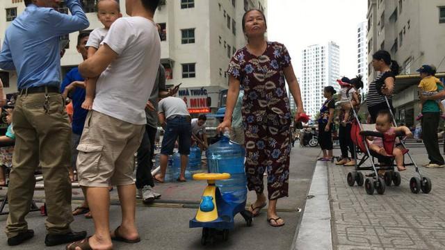 Cư dân Linh Đàm đội mưa nhọc nhằn hứng từng can nước  - Ảnh 11.