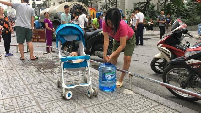 Cư dân Linh Đàm đội mưa nhọc nhằn hứng từng can nước  - Ảnh 6.