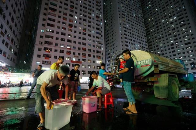 Dân Hà Nội xuyên đêm xếp hàng lấy nước sạch sau vụ nước sông Đà nhiễm dầu - Ảnh 1.