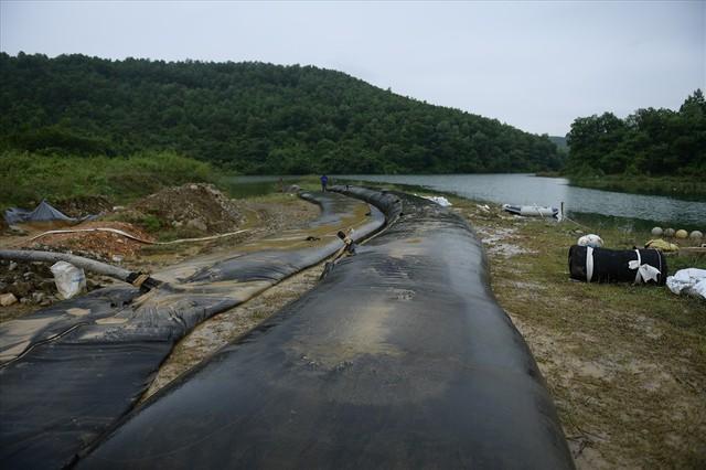 Tiếp tục hút bùn kênh dẫn nước sông Đà sau gần 20 ngày vụ đổ trộm dầu thải - Ảnh 3.