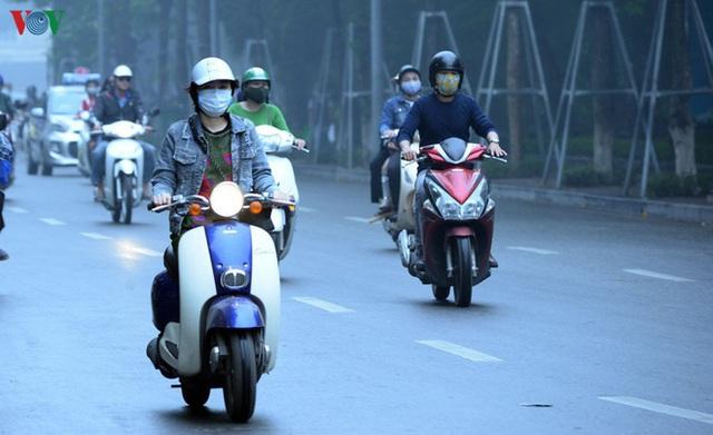 Phố phường Hà Nội chìm trong mịt mù sương, bụi dù vào giữa trưa - Ảnh 12.