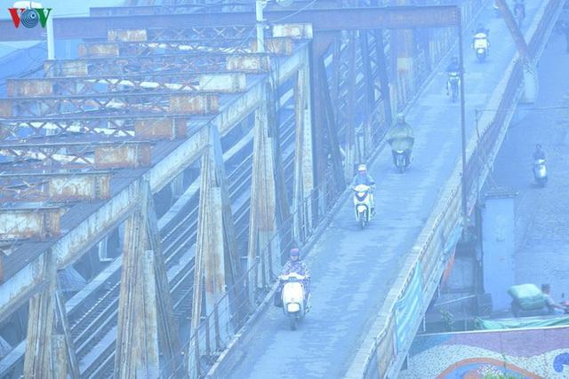 Phố phường Hà Nội chìm trong mịt mù sương, bụi dù vào giữa trưa - Ảnh 3.