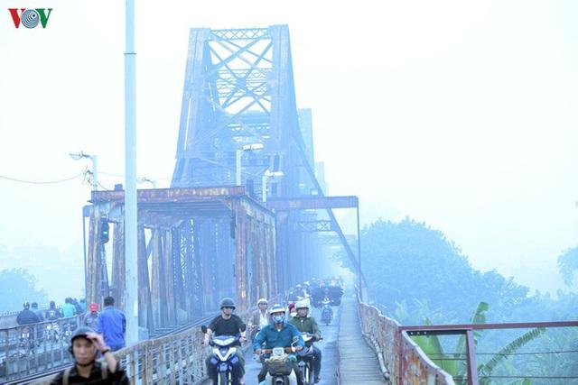 Phố phường Hà Nội chìm trong mịt mù sương, bụi dù vào giữa trưa - Ảnh 4.