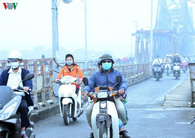 Phố phường Hà Nội chìm trong mịt mù sương, bụi dù vào giữa trưa - Ảnh 6.