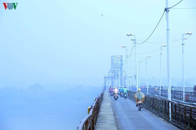 Phố phường Hà Nội chìm trong mịt mù sương, bụi dù vào giữa trưa - Ảnh 7.