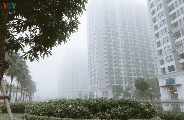 Ảnh: Nhà cao tầng ở Hà Nội mất hút giữa màn sương mù dày đặc - Ảnh 1.