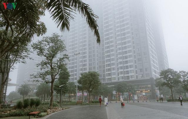 Ảnh: Nhà cao tầng ở Hà Nội mất hút giữa màn sương mù dày đặc - Ảnh 2.