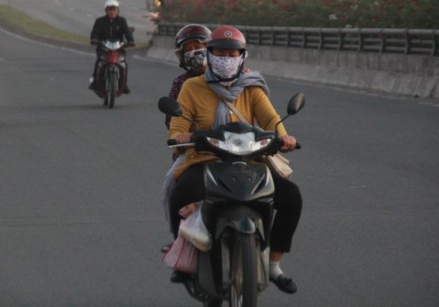 Người Sài Gòn khoác áo mưa, quấn khăn... chống lạnh buổi sáng - Ảnh 1.