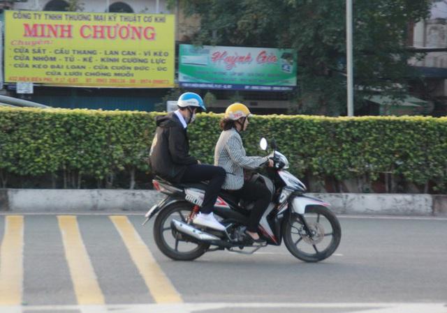 Người Sài Gòn khoác áo mưa, quấn khăn... chống lạnh buổi sáng - Ảnh 12.