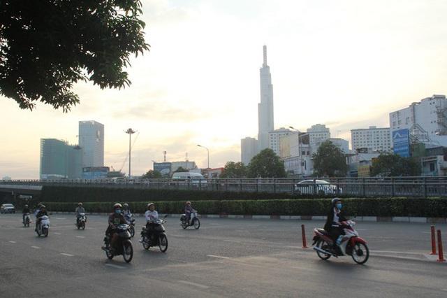 Người Sài Gòn khoác áo mưa, quấn khăn... chống lạnh buổi sáng - Ảnh 14.