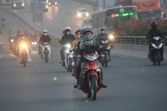 Người Sài Gòn khoác áo mưa, quấn khăn... chống lạnh buổi sáng - Ảnh 3.