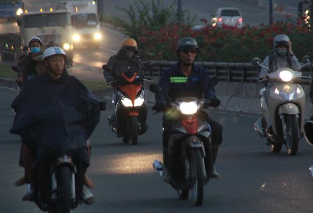 Người Sài Gòn khoác áo mưa, quấn khăn... chống lạnh buổi sáng - Ảnh 4.