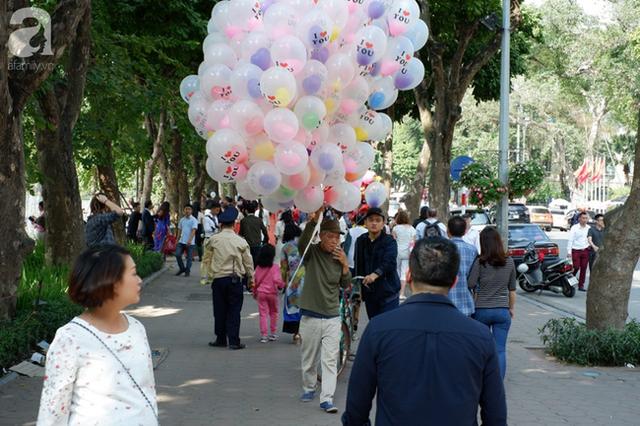 Nắng đẹp, người Hà Nội rủ nhau xuống phố du xuân, xúng xính áo dài chụp ảnh đầu năm mới - Ảnh 1.