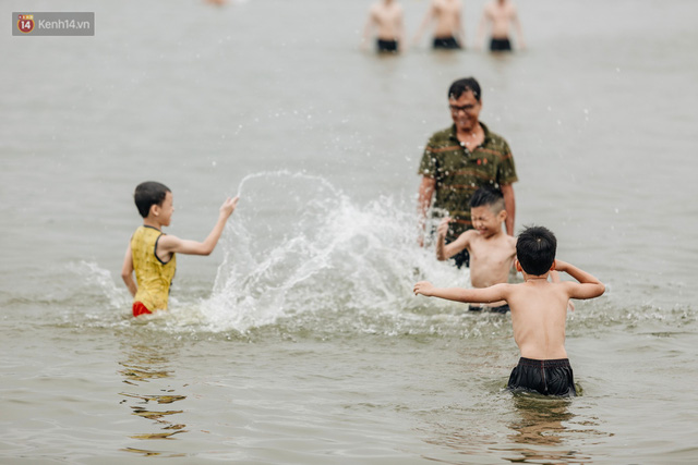 Hà Nội oi nóng ngộp thở, nhiều người mang theo cả thú cưng ra Hồ Tây tắm bất chấp biển cấm - Ảnh 10.