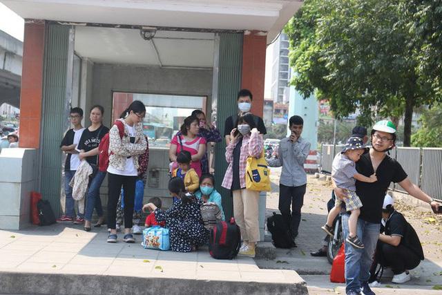 Ôm hoa, vác trẻ, đội nắng đứng ven đường bắt xe về quê nghỉ lễ - Ảnh 2.
