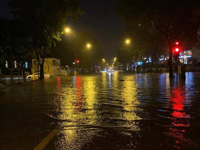 Hà Nội mưa lớn dịp nghỉ lễ 30/4-1/5, nhiều tuyến phố biến thành sông, khách Tây lội bì bõm - Ảnh 1.