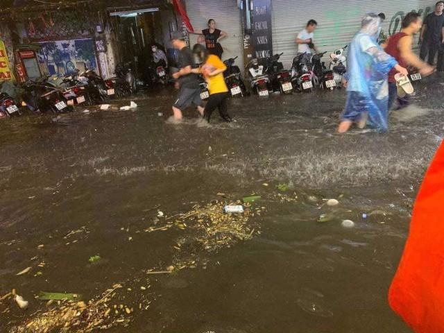 Hà Nội mưa lớn dịp nghỉ lễ 30/4-1/5, nhiều tuyến phố biến thành sông, khách Tây lội bì bõm - Ảnh 2.